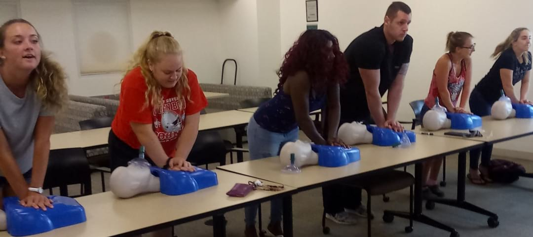 men and women training cpr on dummy