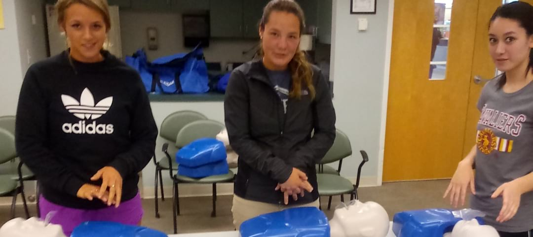 three women with dummy for cpr training